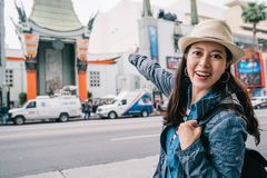 Traveler showing the Chinese Theatre to camera. Traveler joyfully raising her hands and showing the Chinese Theatre to the camera. beautiful woman in blue jacket stock photo