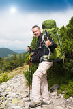 Traveler shows sign OK. Happy hiker winning reaching life goal, success, freedom and happiness, achievement in mountains. Thumbs-up. Sign OK. Hiker with backpack Stock Image