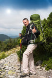 Traveler shows sign OK. Happy hiker winning reaching life goal, success, freedom and happiness, achievement in mountains. Thumbs-up. Sign OK. Hiker with backpack Stock Photos