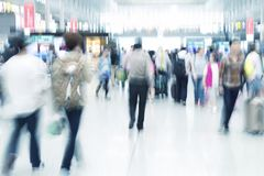 Commuters in motion blur, airport interior. Traveler silhouettes in motion blur, airport interior, blue toned image Royalty Free Stock Photos