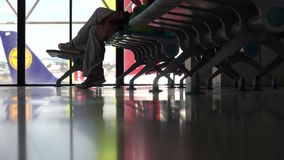 A traveler sits in an airport waiting to catch flight. A typical scene at an airport or mass transit terminal stock video