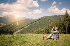 Traveler sits on mountain hill and looking through binocular. Travel and hiking concept stock photo