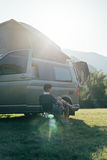 Traveler sits next to camping van in sunset. Young man on folding chair sits on folding chair next to camping tourist van during vacation time, summertime sunset Stock Photo