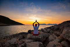 Traveler sits on the rock seashore and practicing yoga during sunset royalty free stock photography