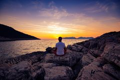 Traveler sits on the rock seashore and practicing yoga royalty free stock images