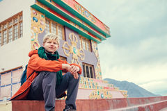 Traveler sits on the stairs of buddhist monastery in Small Tibet Stock Photography