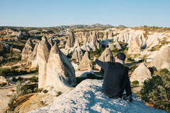 A traveler sits on top of the mountains and shows his hand at a beautiful view in Cappadocia in Turkey. Journey. Hiking. Royalty Free Stock Image