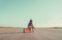 Traveler sits on vintage suitcase Stock Image