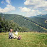 Traveler sitting on the alpine meadow. And looking at the map stock images