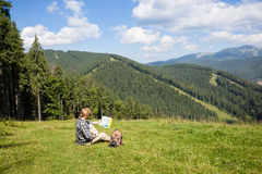 Traveler sitting on the alpine meadow. And looking at the map stock image