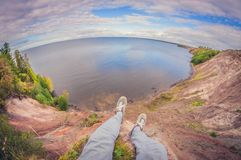 Traveler sitting on a high cliff on the lake, first-person view, fisheye distortion stock images