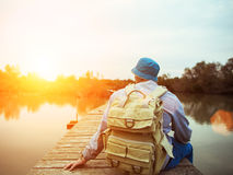 Traveler sitting on the lake on the wooden bridge Royalty Free Stock Images