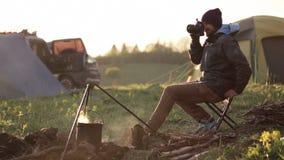 Traveler sitting next to bonfire and taking photo via professional camera. stock video