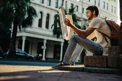 Man exploring the city. Traveler sitting on the pavement looking at a map. Tourist exploring the city with the help of a map royalty free stock images