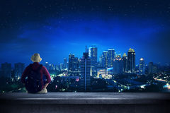 Traveler sitting on the rooftop watching city at night. A traveler sitting on the rooftop watching at the city at night Stock Photography