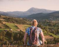 Traveler sitting on wooden fence. At the mountain top stock photography