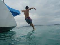 Traveler slides of catamaran Caribbean, Puerto Rico. A teenage boy falls into Caribbean waters, Puerto Rico Royalty Free Stock Photo