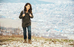 Traveler smiling woman trekking in highlands over the city Royalty Free Stock Images