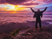 Traveler stand on Rocky cilff with sunsire sky and beautiful cloud sea on `Pa na rai` Khao Luang mountian. Ramkhamhaeng National Park,Sukhothai Province stock photos