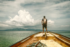 Traveler standing on a boat and looking at the islands Stock Images