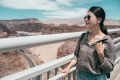 Traveler standing high holding the handrail. Young female backpacker wearing sunglasses sightseeing the nature desert. elegant traveler standing high holding the stock photo
