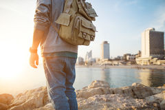 Traveler standing on the rocks near the sea. At sunset and city on background Stock Image