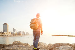 Traveler standing on the rocks near the sea. At sunset and looking at the city Royalty Free Stock Images