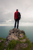 Traveler stands on a cliff and looks at the sea Royalty Free Stock Photos