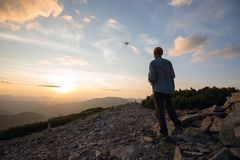Traveler stands in the mountains and controls the drone Stock Images