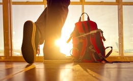 Traveler stands near the backpack at the airport. Stock Photography