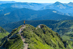 Traveler stands on a ridge, on a background of green mountains Stock Photo
