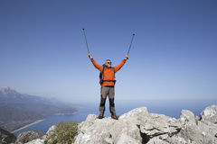 A traveler stands on top of a mountain and looks out to sea. Royalty Free Stock Photography