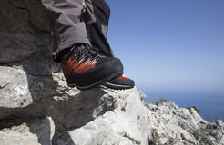 A traveler stands on top of a mountain and looks out to sea. Stock Images