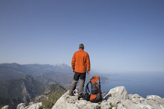 A traveler stands on top of a mountain and looks out to sea. Royalty Free Stock Photos