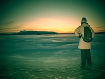 Traveler stay on ice of frozen sea. Woman with backpack. And long warm jacket. Footprints in ice of laggon. Orange sun is rissing above hilly horizon, winter royalty free stock photos