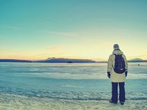 Traveler stay on ice of frozen sea. Woman with backpack. And long warm jacket. Footprints in ice of laggon. Orange sun is rissing above hilly horizon, winter royalty free stock photography