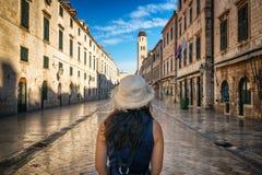 Traveler at Stradun Street in Dubrovnik, Croatia. Traveler walks on the historic street of Stradun (Placa) in old town of Dubrovnik in Croatia - Prominent travel royalty free stock photos