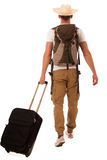 Traveler with straw hat, white shirt, backpack and suitcase walk. Ing away isolated Royalty Free Stock Photo
