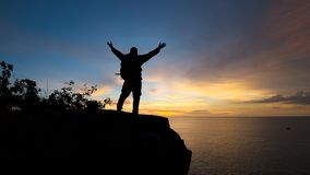 Traveler successful young man show hand standing on top of Mount. Ain and waiting for sunrise stock photo