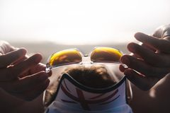 The traveler sunbaths on the beach wearing sunglasses and holds them by hand. Sunglasses close-up, the background is blurred. Sunny Royalty Free Stock Image