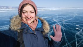 The traveler takes a selfie and waves her hand at the camera of her smartphone. Smiling girl during a trip to the winter Baikal. stock photos