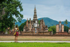 A traveler is taking photo of old Buddhist temple in Sukhothai history park Thailand. Royalty Free Stock Image