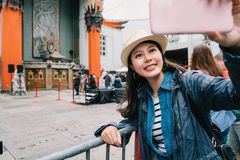 Traveler taking selfie with the Chinese Theatre. Elegant female traveler standing in front of the Chinese Theatre and taking selfie. young girl love taking royalty free stock photography