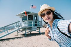 Traveler taking selfie with the lifeguard station. A female traveler taking selfie with the lifeguard station with a big smile stock image