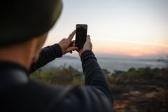 Traveler taking a shots by phone at sunrise. Travel photographer taking a shots by mobile phone at sunrise. Hipster with a little camera in the good light royalty free stock photography