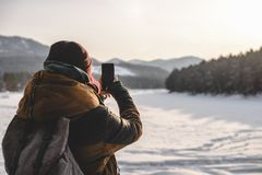 Traveler taking a shots by phone at sunrise. Travel photographer taking a shots by mobile phone at sunrise. Hipster with a little camera in the good light stock photos