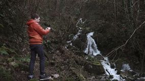 Traveler is taking video by his phone in a forest in fall cold day. Tourist is looking on a small waterfall in autumn forest and shooting on a smartphone. He is stock video