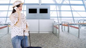 Traveler talking on cellphone at airport terminal. Female traveler standing in the airport terminal while talking on a mobile phone and holding a suitcase stock footage