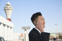 Traveler talking on cellphone outside at airport Royalty Free Stock Photos