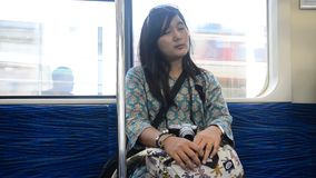 Traveler thai woman sleep on  train from Tokyo city go to Saitama city stock video footage